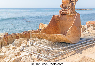 Excavator shovel parked at ocean work site - Close up of...