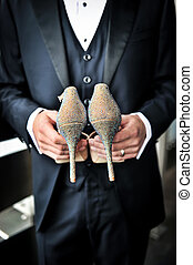 Groom holding bridal shoes - An image of a groom holding...