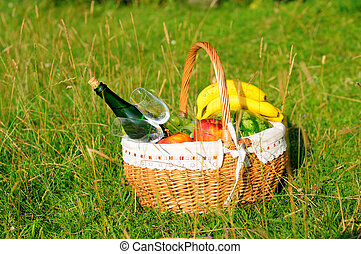 Picnic basket with fruit and wine on green lawn.