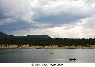 Forest Lake and Boaters - Mountain forest lake among the...