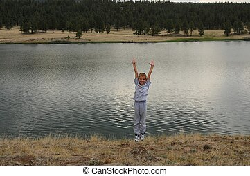 Boy Jumping at Lake - Young boy jumping on shore of mountain...