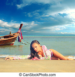 Beautiful woman on the beach with long tail boat