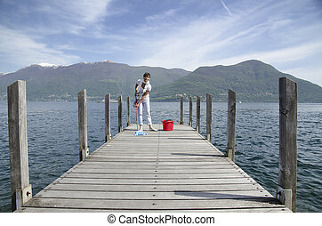 Woman scrubs the pier over the lake with cleaning equipment...