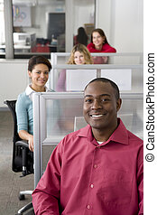 Businessman and co-workers sitting in cubicles