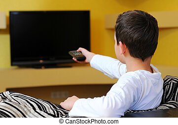 Young Boy - A young boy sitting on the couch watching TV
