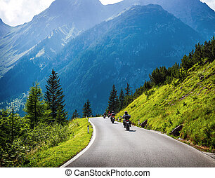 Moto racers on mountainous road - Moto racers riding on...