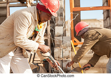 pinched lips in concentration - an young african builder...