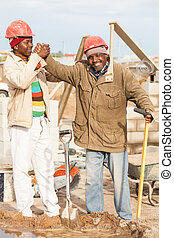 praising the old man - an young african builder praising his...