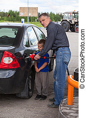 Senior grandfather with young boy refilling car at gas...