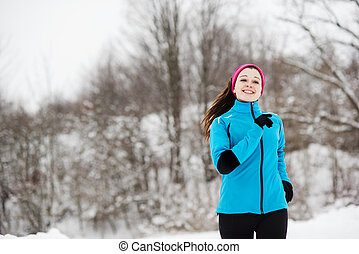 Woman running in winter - Athlete woman is running during...