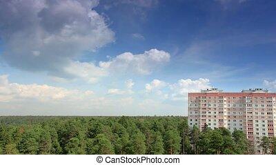 Movement of clouds over the forest, high-rise building,...