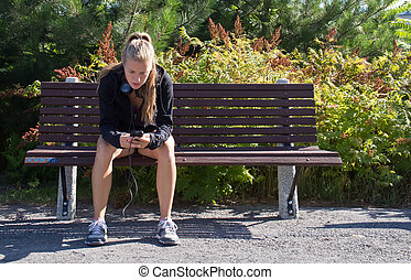 Woman sitting on a bench with smart phone