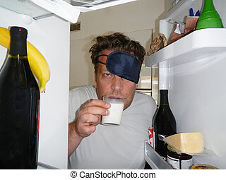 Man with sleep mask drinking milk in the refrigerator -...