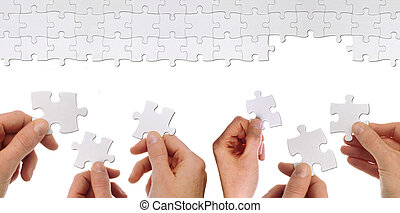 team work concept - some hands hold a part of a puzzles to...