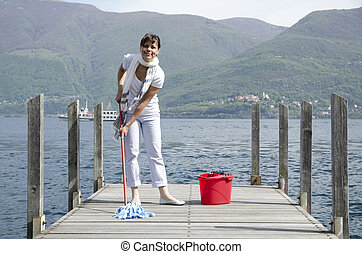 Woman scrubs the pier with cleaning equipment and mountain...