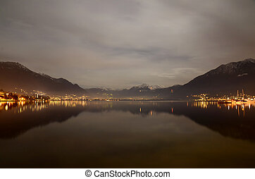 Illuminated alpine lake at night with snow-capped mountain
