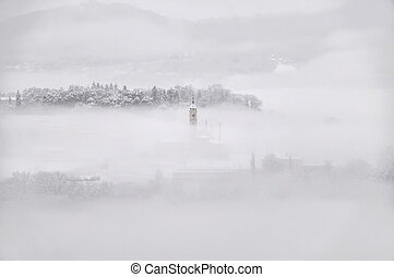 Winter landscape with snow and fog and a tower