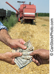 Agricultural concept - Farmer and buyer hands holding dollar...