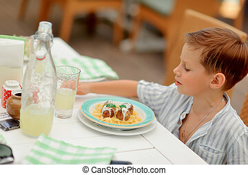 boy eats - at a table in a cafe boy in white shirt eats...
