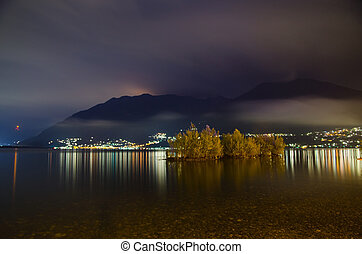 Islands on an alpine lake at night with clouds