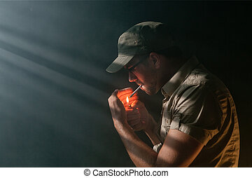 Young Adult lighting a marijuana Joint in the dark