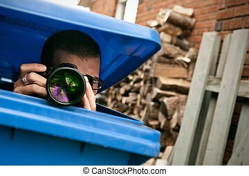 Paparazzi hiding in a blue garbage bin to take pictures