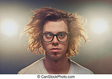 Funny Squinting man with Tousled brown hair in studio using...