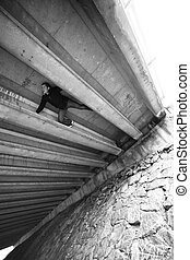 Man doing some Parkour under a bridge structure - Black and...