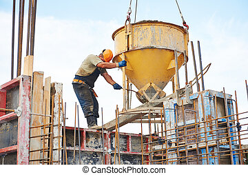building workers pouring concrete with barrel - building...
