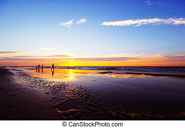 family on the beach during sunset