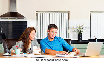 Personal expences - Young couple at the kitchen table, going...
