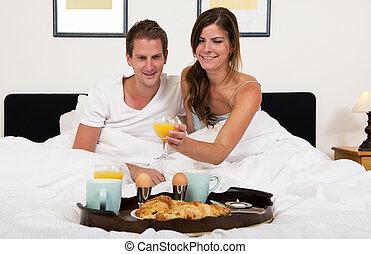 Breakfast in bed - young couple enjoying a rich breakfast in...