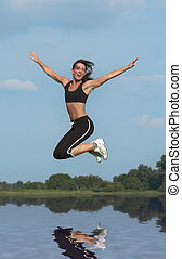 woman jumping above water