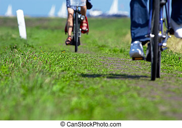 cycling in the netherlands - abstract photo of two people on...