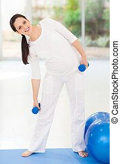 young pregnant woman working out with dumbbells