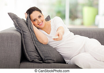 cute pregnant woman watching television - portrait of cute...