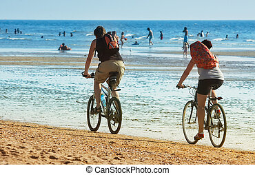 summer cycling - mountain biking on the beach in summer