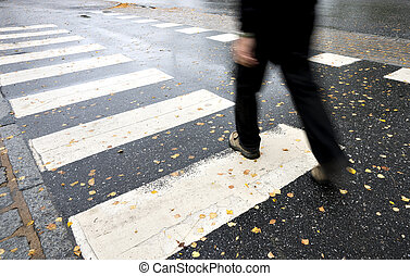 Man crossing street - Man in black crossing street on wet...