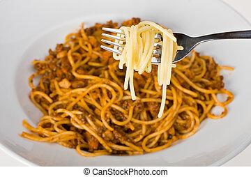 spaghetti - fork over a plate with spaghetti bolognaise