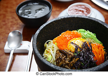 Korean cuisine : bibimbap in a heated stone bowl
