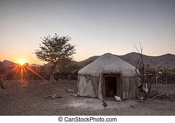 Morning in the village - Sun rises over a mud brick hut in...