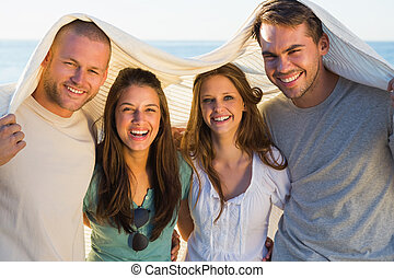 Cheerful group of friends having fun together on the beach