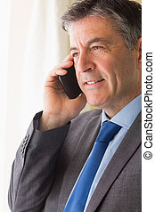 Serious man calling someone with his mobile phone