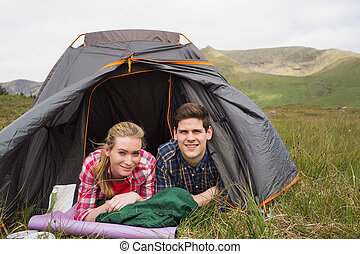 Happy couple lying in their tent after a hike and looking at...