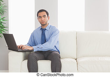 Stern businessman using his laptop while sitting on cozy...