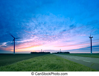 A road through the windmills - A road and windmills during...