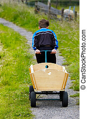 A boy and a wagon - A boy pulling a wagon