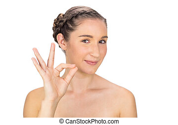 Cheerful woman making okay gesture on white background