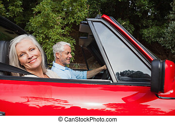 Side view of mature couple driving red convertible on bright...