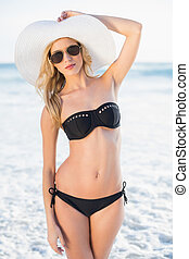Attractive blonde in elegant black bikini posing on a...